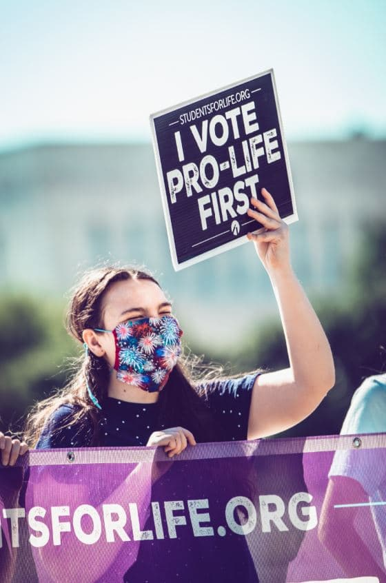 "Young woman holds ""I Vote Pro-Life First"" sign"
